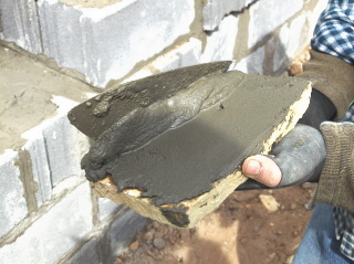 A raised edge of mortar is placed on the side of the rock.