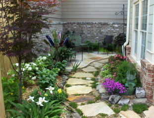 raised beds, perennials, stepping stones leading back to a small flagstone patio
