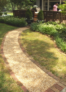 Installation of a pea gravel walkway.  Note the containment border of cemented bricks.