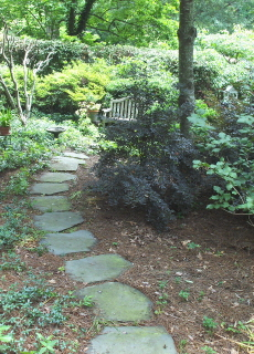 slate stepping stones pave the path to a secluded meditation garden