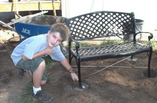 Steven trowels in the cement around the garden bench