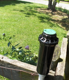 Gear drive sprinkler head mounted to fence for vegetable garden