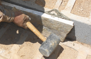set rock upright by tapping with a rubber mallet