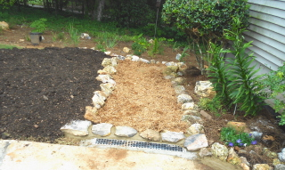 A cypress mulch pathway with rock borders leads to the stepping stones