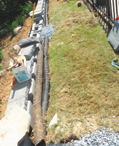 The black drain pipe will direct water into the lower garden instead of causing erosion