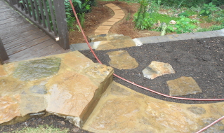 The finished stone walkway with a garden path
