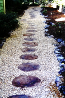 Stepping stones and pea gravel with a rock garden border