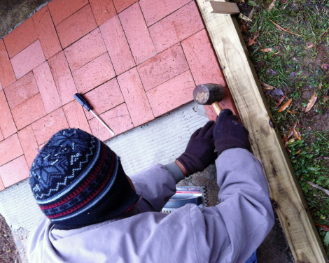 Tapping pavers into place with a rubber mallet