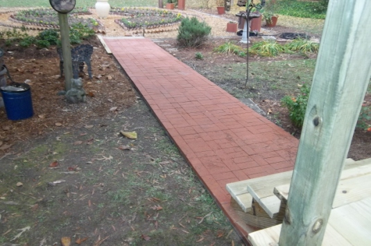 Walkway of brick pavers from deck to garden. Nice