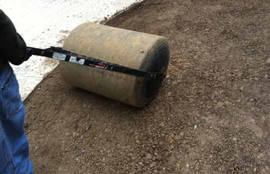 Using a water filled roller to prepare a site for sod