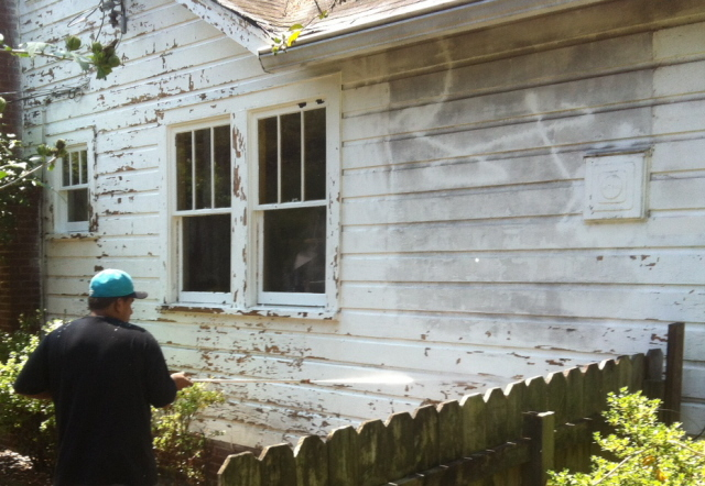 Pressure washing the house in preparation for painting.