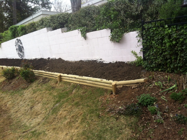 Raised perennial bed with landscape timbers at the base of a retaining wall