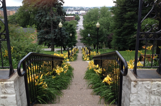 Stairs, lined with yellow daylilies, leading down to the river in Davenport, Iowa