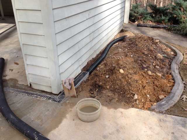 Driveway drainage system being hooked up after concrete pour