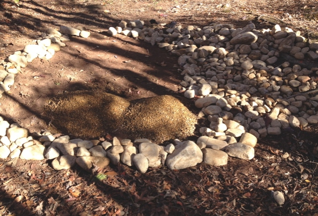 pea gravel will provide a fire proof base and a rock border will hold in the gravel.